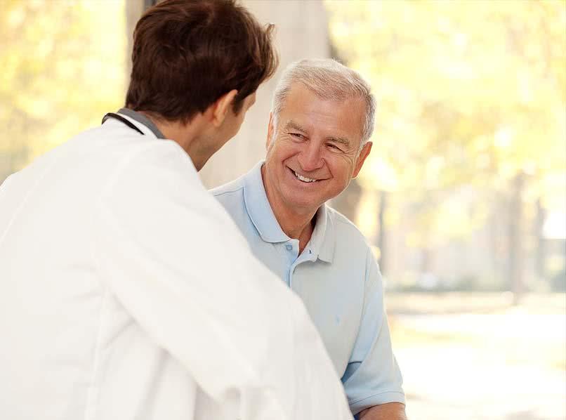 Älterer Patient lächelnd im Gespräch mit jüngerem Arzt