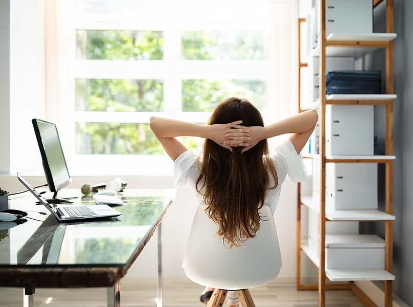 Junge Frau entspannt am Schreibtisch