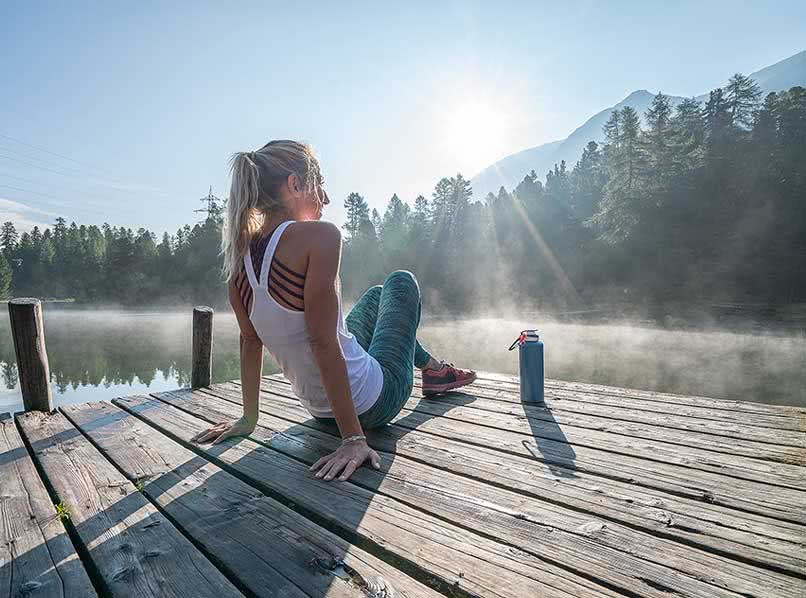 Junge Frau im Sportdress sitzt auf Steg an einem See