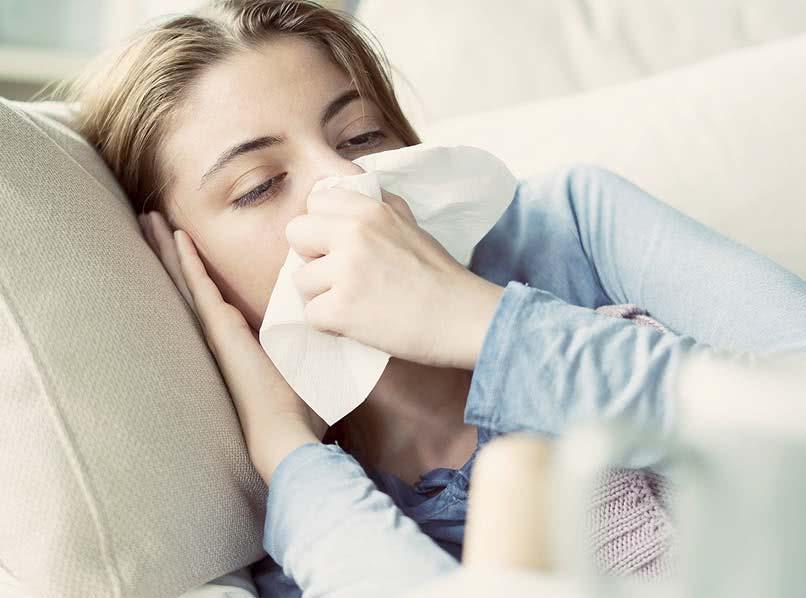 Junge Frau mit Erkältung auf Couch liegend