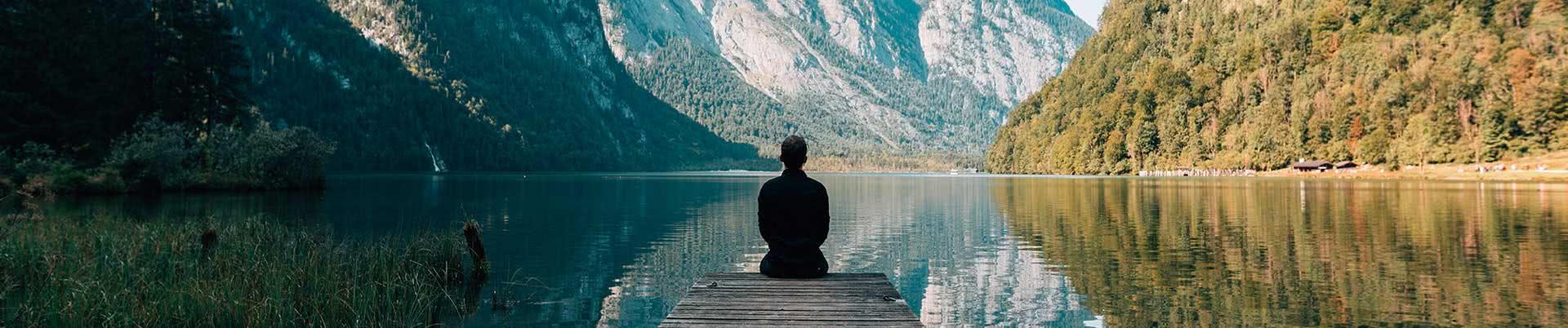 Person sitzt auf einem Steg an einem Bergsee