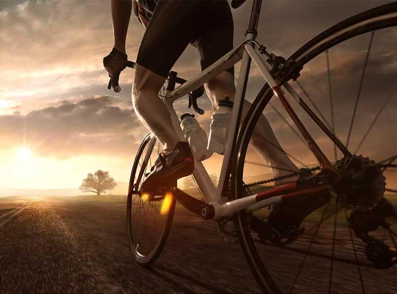 Rennradfahrer fährt auf einer Landstraße der Sonne entgegen