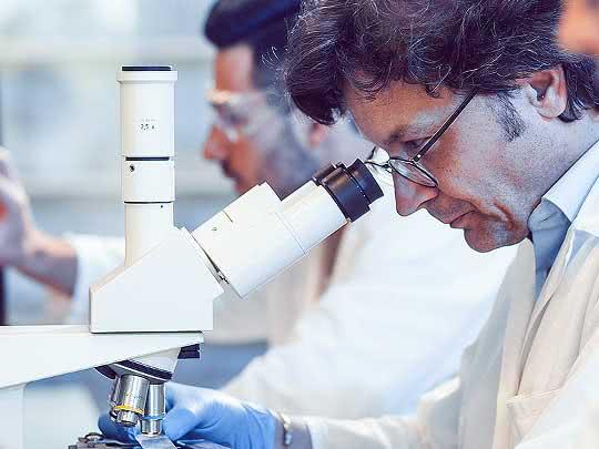 Laborant schaut in ein Mikroskop