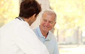 Älterer Patient lächelnd im Gespraech mit jungem Arzt