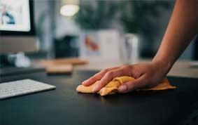 Hand mit Putztuch wischt Schreibtisch